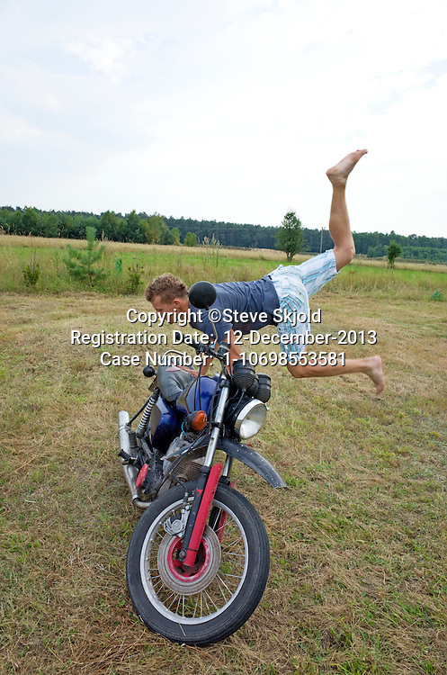 Polish teen boy performing acrobatic moves on his motorcycle. Zawady Central Poland