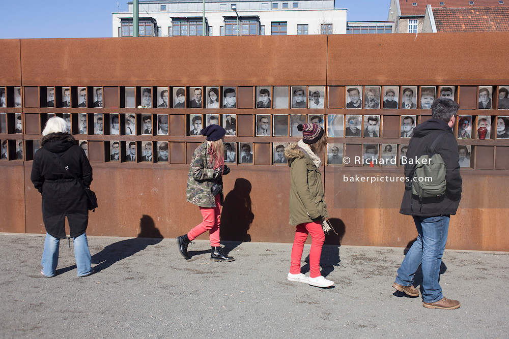 """The faces and names of those killed while trying to cross  Berlin Wall, the former border between Communist East and West Berlin during the Cold War. The Berlin Wall was a barrier constructed by the German Democratic Republic (GDR, East Germany) starting on 13 August 1961, that completely cut off (by land) West Berlin from surrounding East Germany and from East Berlin. The Eastern Bloc claimed that the wall was erected to protect its population from fascist elements conspiring to prevent the """"will of the people"""" in building a socialist state in East Germany. In practice, the Wall served to prevent the massive emigration and defection that marked Germany and the communist Eastern Bloc during the post-World War II period."""