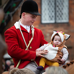 © Licensed to London News Pictures. 26/12/2018. Market Bosworth, UK. Boxing Day Hunt meet. Pictured, Huntsman Conrad Jones and his daughter Erin (five months). The traditional Boxing Day Hunt meet took part in Market Bosworth, Leicestershire, earlier today. Riders of all ages took part in the parade. Meeting in the market square, they visited a near by care home taking their hounds to meet residents. The Hunt formed up in pairs and rode through the town centre passing huge Boxing Day crowds that had come to see the spectacle. Photo credit: Dave Warren/LNP