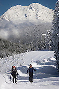 Jon De Armin and Doug Savage ski to Snow Bowl Hut of the Mount Tahoma Trails crosscountry ski and snowshoe hut-to-hut trail system in the Tahoma State Forest with Mount Rainier in the background, Washington state, USA