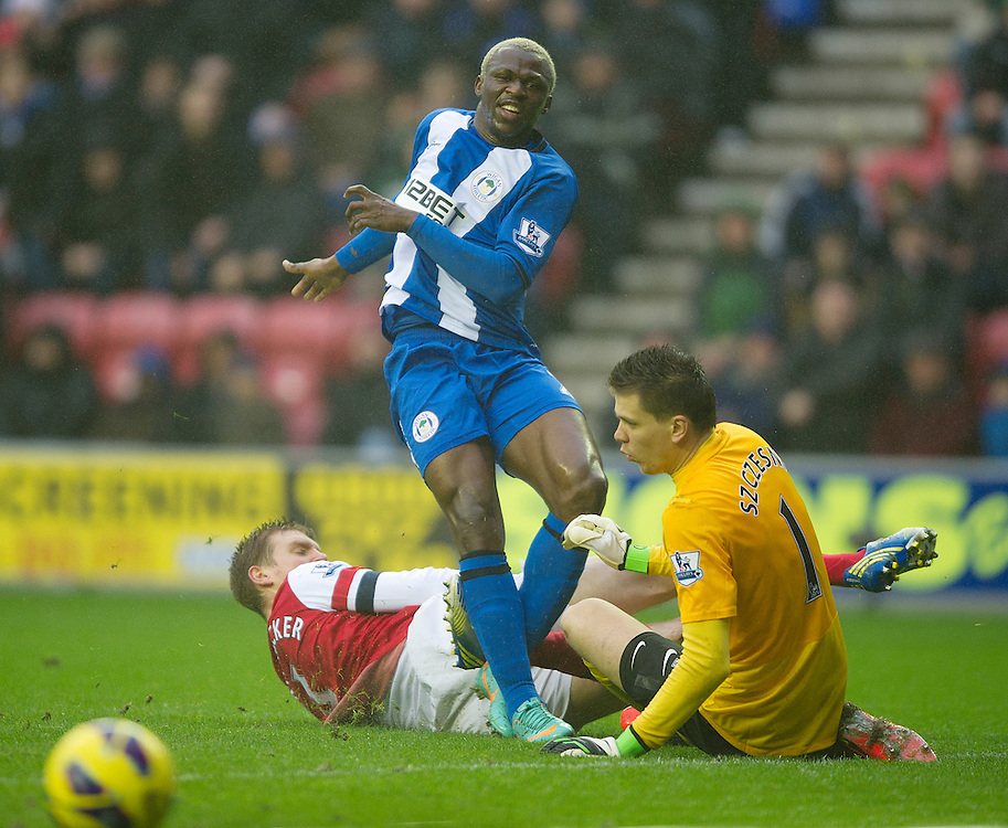 Arsenal's Per Mertesacker and goalkeeper Wojciech Szczesny do enough to cause Wigan Athletic's Arouna Kone to shoot just wide of the goal..Football - Barclays Premiership - Wigan Athletic v Arsenal - Saturday 22nd December 2012 - DW Stadium - Wigan..