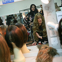 Miri Beillin, an ultra orthodox Jewish woman, works as a stylist during a fashion show for ultra orthodox women. miri tries on a new wig behind the scenes.