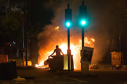 "© Licensed to London News Pictures. 28/07/2017. London, UK. Protesters take to the streets of Dalston setting mattress on fire as they clash with police following the death of Rashan Charles whilst being arrested by police.  A statement from Scotland Yard said Mr Charles went into a shop, where he was seen ""trying to swallow an object"" and it was then police officers struggled with him to make an arrest. Photo credit: Ray Tang/LNP"