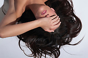 Close up of prone woman covering her eyes with her brunette hair spread out