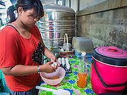 "28 OCTOBER 2014 - BANGKOK, THAILAND: A worker opens eggs to make batter at the Pajonglak Maneeprasit Bakery in Bangkok. The cakes are called ""Kanom Farang Kudeejeen"" or ""Chinese Monk Candy."" The tradition of baking the cakes, about the size of a cupcake or muffin, started in Siam (now Thailand) in the 17th century AD when Portuguese Catholic priests accompanied Portuguese soldiers who assisted the Siamese in their wars with Burma. Several hundred Siamese (Thai) Buddhists converted to Catholicism and started baking the cakes. When the Siamese Empire in Ayutthaya was sacked by the Burmese the Portuguese and Thai Catholics fled to Thonburi, in what is now Bangkok. The Portuguese established a Catholic church near the new Siamese capital. Now just three families bake the cakes, using a recipe that is 400 years old and contains eggs, wheat flour, sugar, water and raisins. The same family has been baking the cakes at the Pajonglak Maneeprasit Bakery, near Santa Cruz Church, for more than 245 years. There are still a large number of Thai Catholics living in the neighborhood around the church.   PHOTO BY JACK KURTZ"