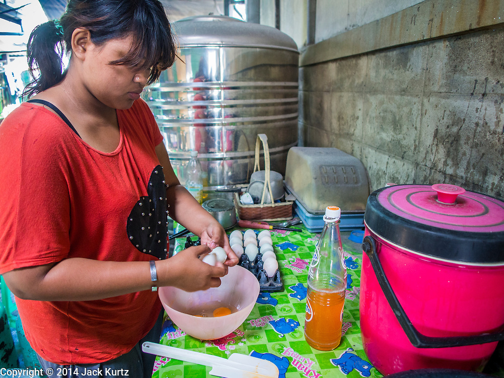 """28 OCTOBER 2014 - BANGKOK, THAILAND: A worker opens eggs to make batter at the Pajonglak Maneeprasit Bakery in Bangkok. The cakes are called """"Kanom Farang Kudeejeen"""" or """"Chinese Monk Candy."""" The tradition of baking the cakes, about the size of a cupcake or muffin, started in Siam (now Thailand) in the 17th century AD when Portuguese Catholic priests accompanied Portuguese soldiers who assisted the Siamese in their wars with Burma. Several hundred Siamese (Thai) Buddhists converted to Catholicism and started baking the cakes. When the Siamese Empire in Ayutthaya was sacked by the Burmese the Portuguese and Thai Catholics fled to Thonburi, in what is now Bangkok. The Portuguese established a Catholic church near the new Siamese capital. Now just three families bake the cakes, using a recipe that is 400 years old and contains eggs, wheat flour, sugar, water and raisins. The same family has been baking the cakes at the Pajonglak Maneeprasit Bakery, near Santa Cruz Church, for more than 245 years. There are still a large number of Thai Catholics living in the neighborhood around the church.   PHOTO BY JACK KURTZ"""