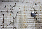 Cracked and split tiling on the wall under a railway bridge in south London.