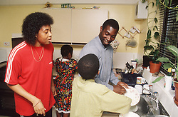 Family group in kitchen with father and young son doing washing up,