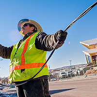 121113       Cable Hoover<br /> <br /> Leo Lucero strings out a length of new cable as a City of Gallup electric crew installs new, energy efficient LED street lamps on Aztec Avenue in downtown Gallup Wednesday.