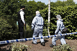 © Licensed to London News Pictures. 21/05/2019. London, UK. Forensics officers are seen on waste land next to a metal shed near Feltham in west London where a body was discovered. Reports say the victim was found next to a burnt out metal corrugated shed in the early hours of this morning. Photo credit: Peter Macdiarmid/LNP