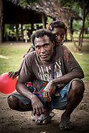 A man and young girl holding a red balloon in a village on the lower Ramu River in Madang Province, Papua New Guinea (2017)
