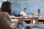 VSO volunteer Paul Jennings and local teacher Rebecca Ngovano in discussion during a training session for all the teachers in the school to improve teaching methodologies in classrooms. Angaza school, Lindi, Tanzania