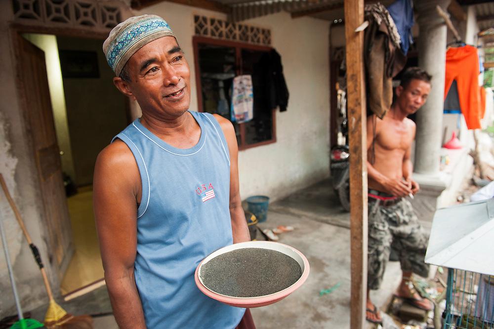 Darman (53 years old) is a miner since 22 years. He earns 6 euros a day. Here with the tin he found on 1 day. <br /> Bangka Island (Indonesia) is devastated by illegal tin mines. The demand for tin has increased due to its use in smart phones and tablets.<br /> <br /> Darman (53 ans). Mineur depuis 22 ans. Gagne 6 euro par jour. <br /> L'île de Bangka (Indonésie) est dévastée par des mines d'étain sauvages. la demande de l'étain a explosé à cause de son utilisation dans les smartphones et tablettes