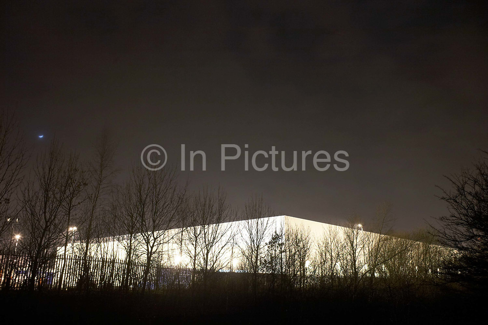 The form of a giant generic warehouse glows from ambient light at the DIRFT warehouse logistics park in Daventry, Northamptonshire England. Bare trees without foliage are seen in the foreground on this cold winter night. We see the building low in the picture and the sky graduates from light into near darkness. This 365 acre site off Junction 18 of the M1 motorway is a hub for road, rail and service infrastructure, some 2.3m sq.ft. of distribution and manufacturing floorspace had been constructed by 2004 and occupiers including Tesco's, Tibbett & Britten plc, Ingram Micro, Royal Mail, the W.H. Malcolm Group, Eddie Stobart Ltd, Wincanton and Exel, have been attracted to this unique logistics location.