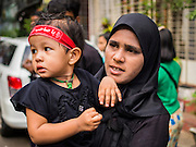 03 NOVEMBER 2014 - YANGON, MYANMAR:  Shia Muslims in Yangon watch an Ashura procession Monday. Shia Muslims in Yangon started the celebration of Ashura Monday. Ashura commemorates the death of Hussein ibn Ali, the grandson of the Prophet Muhammed, in the 7th century. Hussein ibn Ali is considered by Shia Muslims to be the third Imam and the rightful successor of Muhammed. He was killed at the Battle of Karbala in 610 CE on the 10th day of Muharram, the first month of the Islamic calendar. According to Myanmar government statistics, only about 4% of Myanmar is Muslim. Many Muslims have fled Myanmar in recent years because of violence directed against Burmese Muslims by Buddhist nationalists.   PHOTO BY JACK KURTZ