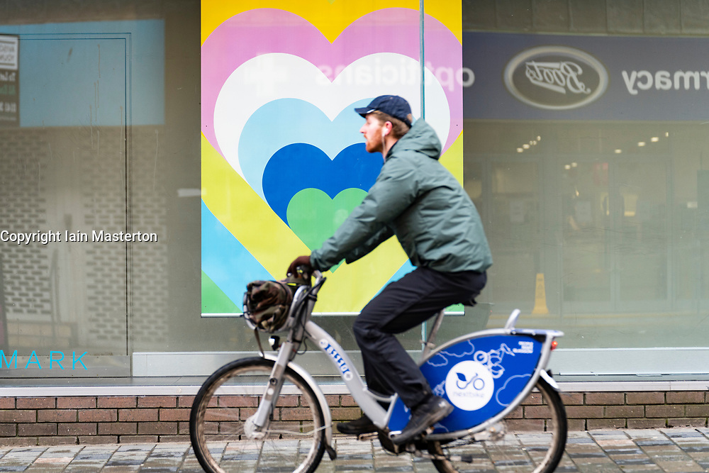 Glasgow, Scotland, UK. 12 March 2021. On the day Covid-19 lockdown is relaxed slightly in Scotland the city centre streets in Glasgow city centre remain almost deserted virtually all shops ad cafes are still closed. Pic;  Cyclist rides past heart poster in shop window. Iain Masterton/Alamy Live News