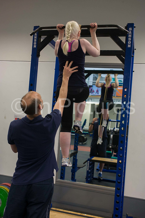 Partially-sighted skiing paralympian from the Sochi Olympics, Kelly Gallagher trains with her trainer in the gym at the Sports Institute, University of Ulster, Northern Ireland, UK. Helped by her trainer, she practices pull-ups to help build thigh strength while starting a new training regime for the forthcoming winter season. Kelly Marie Gallagher, MBE is a Northern Irish skier and the first athlete from Northern Ireland to compete in the Winter Paralympics. Gallagher won Britain's first ever Winter Paralympic gold medal during Sochi 2014.
