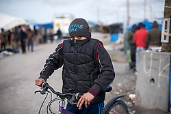 © London News Pictures. 29/04/2016. Calais, France. 11 year-old Unaccompanied child refugee Afghan boy Azim  riding his bike in the calais Jungle. David Cameron has announced Britain will take in some child refugees living in camps inside the EU. Photo credit: Ben Cawthra/LNP