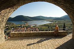 Europe, Croatia, Dalmatia, Mali Ston.  Female tourist gazes at salt pans, lush hills and village of Mali Ston, from arch in 15th century fort.  MR
