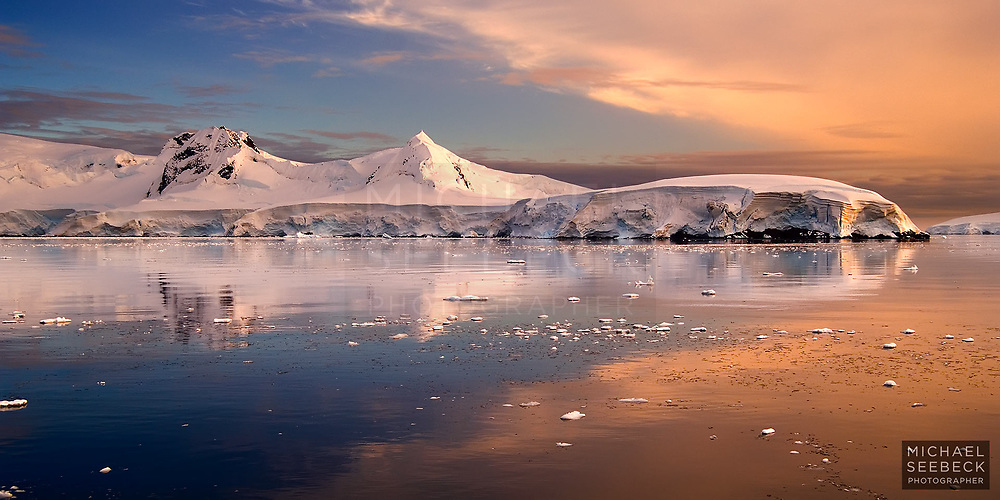 A beautiful sunrise is unfolds over a calm Antarctic sea, with icy mountains & glaciers reflected on the calm water.<br /> <br /> Code: BATW0001<br /> <br /> Limited Edition Print