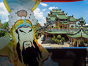 24 AUGUST 2014 - BANGKOK, THAILAND:  A painting of Confucius on the door of a pagoda at the Chee Chin Khor temple in Bangkok with the temple's main hall in the background. Chee Chin Khor Moral Up-Lifting for Benefiction Foundation in a Chinese style temple on the Thonburi side of the Chao Phraya River in Bangkok. It blends aspects of Taoism, Buddhism (both Theravada and Mahayana), Islam, and Christianity religious traditions. Members of the temple perform community services throughout Bangkok.       PHOTO BY JACK KURTZ