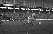 Kerry kicks the ball as Dublin runs into him during the All Ireland Senior Gaelic Football Final, Kerry v Dublin in Croke Park on the 28th September 1975. Kerry 2-12 Dublin 0-11.