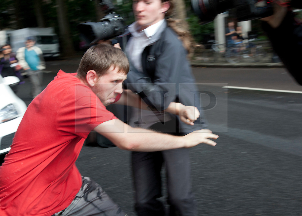 © Licensed to London News Pictures. 11/08/2011. LONDON, UK. David O'Neill pushes his way through photographers after hiding from media inside Westminster Magistrates Court. He was given bail after allegedly throwing missiles at police during the London Riots. Photo credit: Matt Cetti-Roberts/LNP