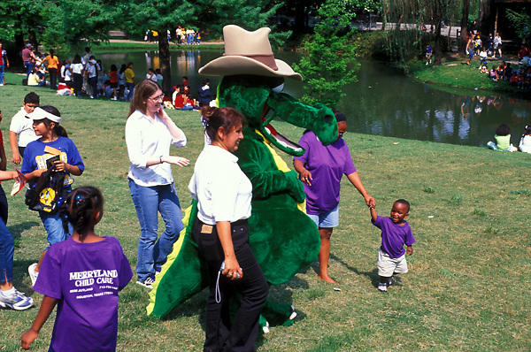 Stock photo of a crowd of children meeting the alligator mascot at the International Festival in downtown Houston Texas