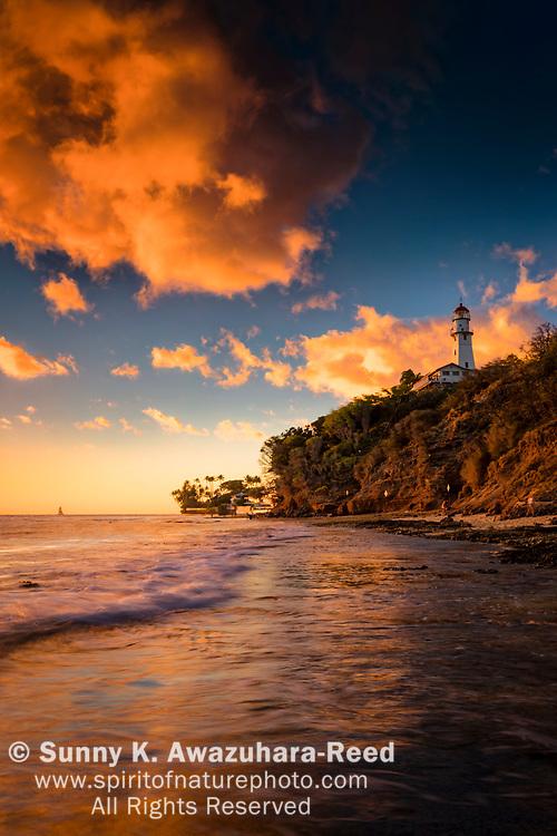 Crimson clouds over Diamond Head Lighthouse and Diamond Head Beach Park at sunset. Honolulu, Oahu Island, Hawaii.