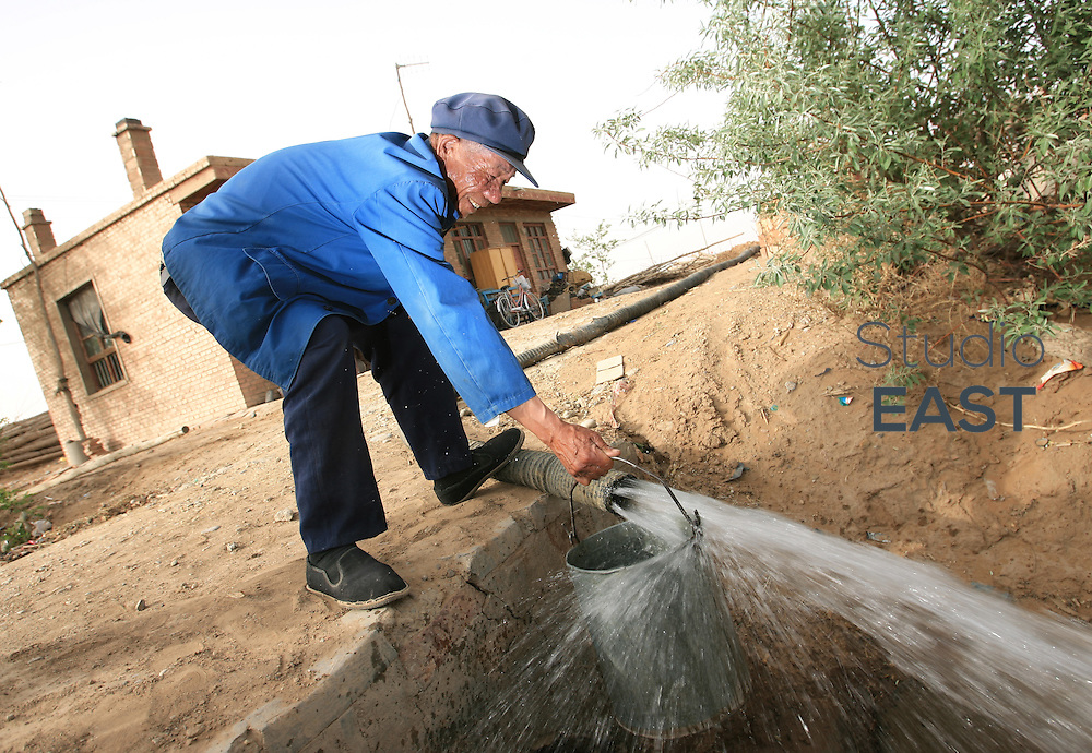 NINGXIA PROVINCE, CHINA - May 08: 70-year old farmer Qi Shenglian gets water from a deep well dug in the ground of what used to be the Tengeli desert on May 8, 2007 in Ningxia Province, China. China is the only place in the world where desert is shrinking, not expanding, thanks to active anti-desertification campaigns. (Photo by Lucas Schifres/Getty Images)