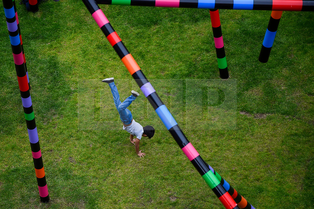 """© Licensed to London News Pictures. 16/07/2020. LONDON, UK.  Zeph, aged 5, performs cartwheels at the unveiling of """"My World and Your World"""", by major contemporary London-based, Irish artist Eva Rothschild.  The new 16m high public sculpture in Lewis Cubitt Park in King's Cross resembles a lightning bolt, painted in black, purple, pink, orange, green and red stripes.  The coronavirus lockdown caused the April 2020 launch to be postponed, but the unveiling has been able to go ahead now that certain lockdown restrictions have been eased by the UK government. (Permission granted). Photo credit: Stephen Chung/LNP"""