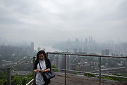 A woman stands on a tourist platform overlooking the city in Chongqing, China, on Thursday, April 14, 2016. The municipality of 30 million people saw state-led development approach fueled the fastest pace nationwide, with President Xi Jinping praising policy innovations that have included subsidized housing and relaxed residency rules that encourage labor mobility.