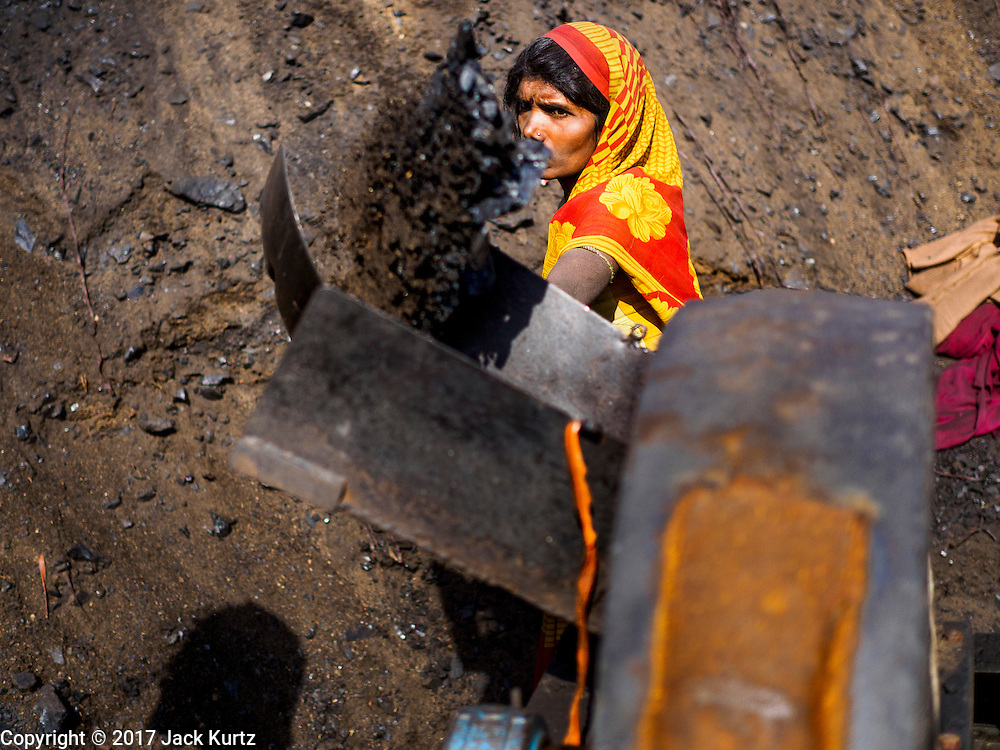 03 MARCH 2017 - BAGMATI, NEPAL: A worker shovel coal into a grinder that makes coal dust at a brick factory in Bagmati, near Bhaktapur. There are almost 50 brick factories in the valley near Bagmati. The brick makers are very busy making bricks for the reconstruction of Kathmandu, Bhaktapur and other cities in the Kathmandu valley that were badly damaged by the 2015 Nepal Earthquake. The brick factories have been in the Bagmati area for centuries because the local clay is a popular raw material for the bricks. Most of the workers in the brick factories are migrant workers from southern Nepal.       PHOTO BY JACK KURTZ