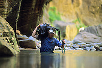 A hiker wades through a deep pool while exploring the Virgin River Narrows in Zion National Park, Utah.