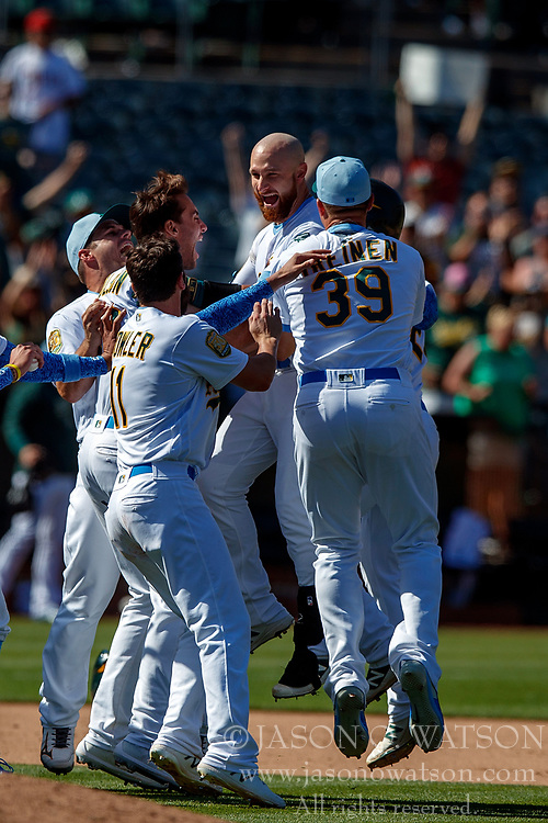 OAKLAND, CA - JUNE 17:  Jonathan Lucroy #21 of the Oakland Athletics celebrates with teammates after hitting a walk off single against the Los Angeles Angels of Anaheim during the eleventh inning at the Oakland Coliseum on June 17, 2018 in Oakland, California. The Oakland Athletics defeated the Los Angeles Angels of Anaheim 6-5 in 11 innings. (Photo by Jason O. Watson/Getty Images) *** Local Caption *** Jonathan Lucroy