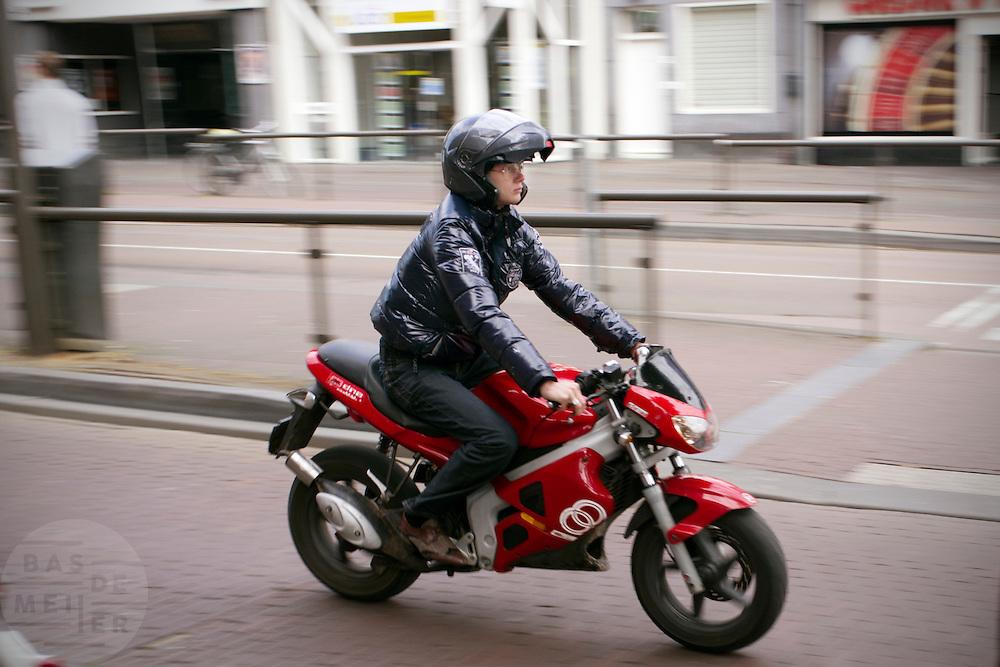 Een jongen rijdt op een brommer door het centrum van Utrecht.<br /> <br /> A guy on a moped in Utrecht.