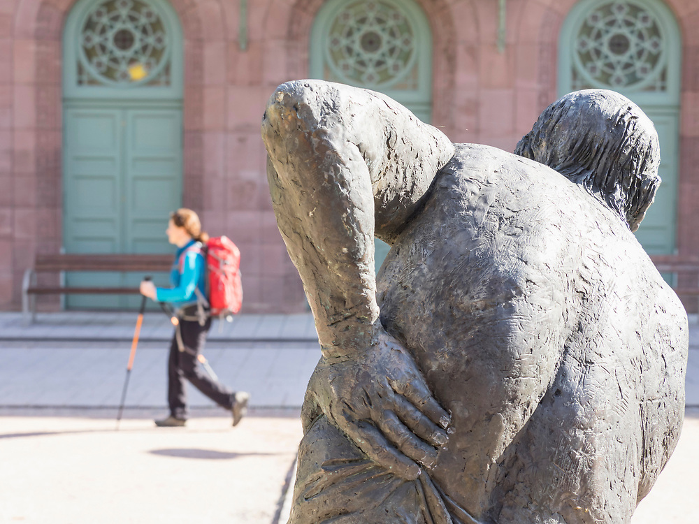 Woman on hiking tour passing by statue and building of Palais-Thermal in the Northern Black Forest, Bad Wildbad, Baden-Württemberg, Germany