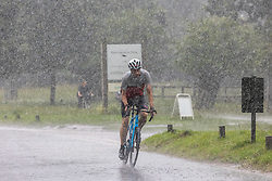 Licensed to London News Pictures. 12/07/2021. London, UK. A cyclist gets caught in torrential rain in Richmond Park, southwest London this afternoon with roads and pavements becoming quickly flooded as the Met Office issue yellow weather warnings for heavy rain and thunderstorms which may cause disruption to travel and flooding. However, sunshine and warm weather is predicted for the rest of the week with highs of 26c for the weekend.. Photo credit: Alex Lentati/LNP