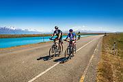 Cycling under the Southern Alps along the Tekapo Canal, Lake Tekapo, Canterbury, South Island, New Zealand