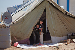 © Licensed to London News Pictures. 12/05/2013. Dohuk, Iraq. Syrian refugees are seen in the entrance to their tent at a refugee camp in Iraqi-Kurdistan, set up for Syrians escaping the ongoing civil war. The camp, close to the city of Dohuk, now houses in the region of 45,000 refugees, with around 400 new arrivals every day. Photo credit: Matt Cetti-Roberts/LNP