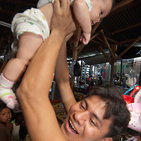 A vendor hoists his baby  in the  outdoor market in upper Belem, a crowded neighborhood in Iquitos, Peru.