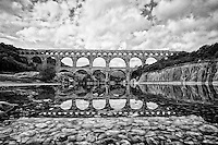 Black and white view of Pont du Gard (Roman Aqueduct), taken from the reflective waters of the Gardon River, Vers-Pont-du-Gard, France.