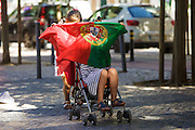 Portuguese children celebrating with national flag in a street in Lisbon. Portugal's national squad won the Euro Cup the day before, beating in the final France, the organizing country of the European Football Championship, in a match that ended 1-0 after extra-time.