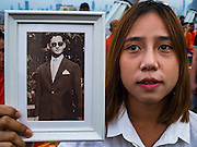 05 DECEMBER 2016 - BANGKOK, THAILAND:  A woman holds up a portrait of the late King while she prays during a ceremony honoring His Majesty on Bhumibol Bridge. Tens of thousands of Thais gathered on Bhumibol Bridge in Bangkok Monday to mourn the death of Bhumibol Adulyadej, the Late King of Thailand. The King died on Oct 13 after a lengthy hospitalization. December 5 is his birthday and a national holiday in Thailand. The bridge is named after the late King, who authorized its construction. 999 Buddhist monks participated in a special merit making ceremony on the bridge.      PHOTO BY JACK KURTZ