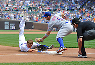 Third baseman David Wright #5 of the New York Mets (C) tags out Ryan Sweeney #6 of the Chicago Cubs at third base as third base umpire Manny Gonzalez (R) looks to make the call during the fourth inning on May 19, 2013 at Wrigley Field in Chicago, Illinois.  Sweeney tried to stretch a double into a triple.    (Getty Images)