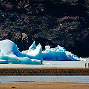 Hikers and Icebergs in Lago Grey in the Torres del Paine national Park, Patagonia, Chile.