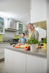 Mother cutting vegetables with her son, smiling