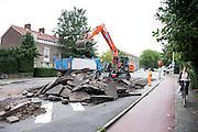 Bij de David van Mollemweg in Utrecht worden grote brokken asfalt afgevoerd. Het wegdek wordt grondig gerenoveerd.<br /> <br /> An excavator is putting asphalt in  truck