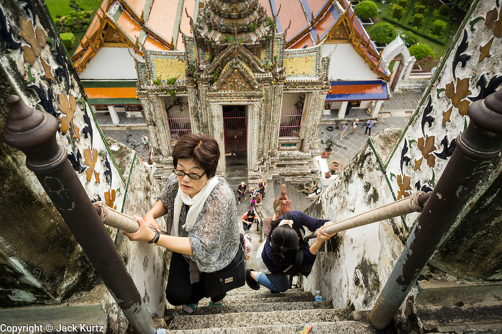 """23 SEPTEMBER 2013 - BANGKOK, THAILAND: Tourists climb the stairs of the famous central chedi at Wat Arun on the last day the stupa would be open for climbing. The full name of the temple is Wat Arunratchawararam Ratchaworamahavihara. The outstanding feature of Wat Arun is its central prang (Khmer-style tower). The world-famous stupa, known locally as Phra Prang Wat Arun, will be closed for three years to undergo repairs and renovation along with other structures in the temple compound. This will be the biggest repair and renovation work on the stupa in the last 14 years. In the past, even while large-scale work was being done, the stupa used to remain open to tourists. It may be named """"Temple of the Dawn"""" because the first light of morning reflects off the surface of the temple with a pearly iridescence. The height is reported by different sources as between 66,80 meters and 86 meters. The corners are marked by 4 smaller satellite prangs. The temple was built in the days of Thailand's ancient capital of Ayutthaya and originally known as Wat Makok (The Olive Temple). King Rama IV gave the temple the present name Wat Arunratchawararam. Wat Arun officially ordained its first westerner, an American, in 2005. The central prang symbolizes Mount Meru of the Indian cosmology. The temple's distinctive silhouette is the logo of the Tourism Authority of Thailand.           PHOTO BY JACK KURTZ"""