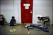 """.Exhausted and upset with their performance, members of the Santa Fe High School Demon Heat dance and drill team (from left) Melanie Serrano, Chrystlyn Griego, Tamara Ortega and Mikaila Tauber rest outside locker rooms in The Pit during the state high school basketball tournament. The team had just performed a half-time routine Thursday. """"When you put everything you've got into two minutes, it wears you out,"""" coach Linda Borrego said."""